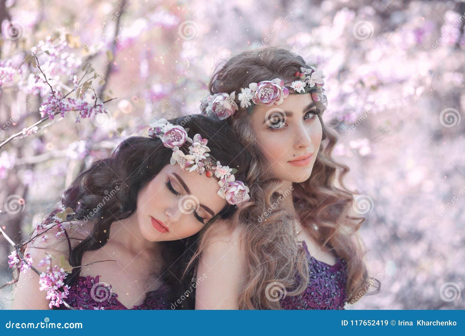 Dos novias, blonde y una morenita, con el amor abrazándose Fondo de un jardín floreciente hermoso de la lila El Princ