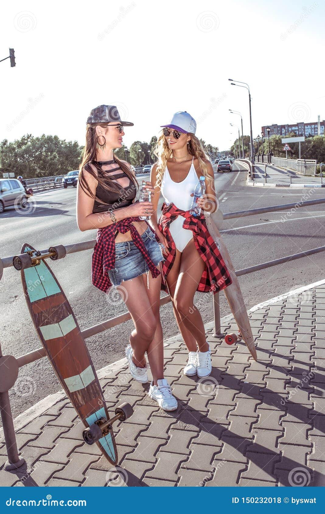Dos novias de las muchachas que sostienen las botellas de agua, coches del monopatín del camino del fondo, figuras bronceadas her