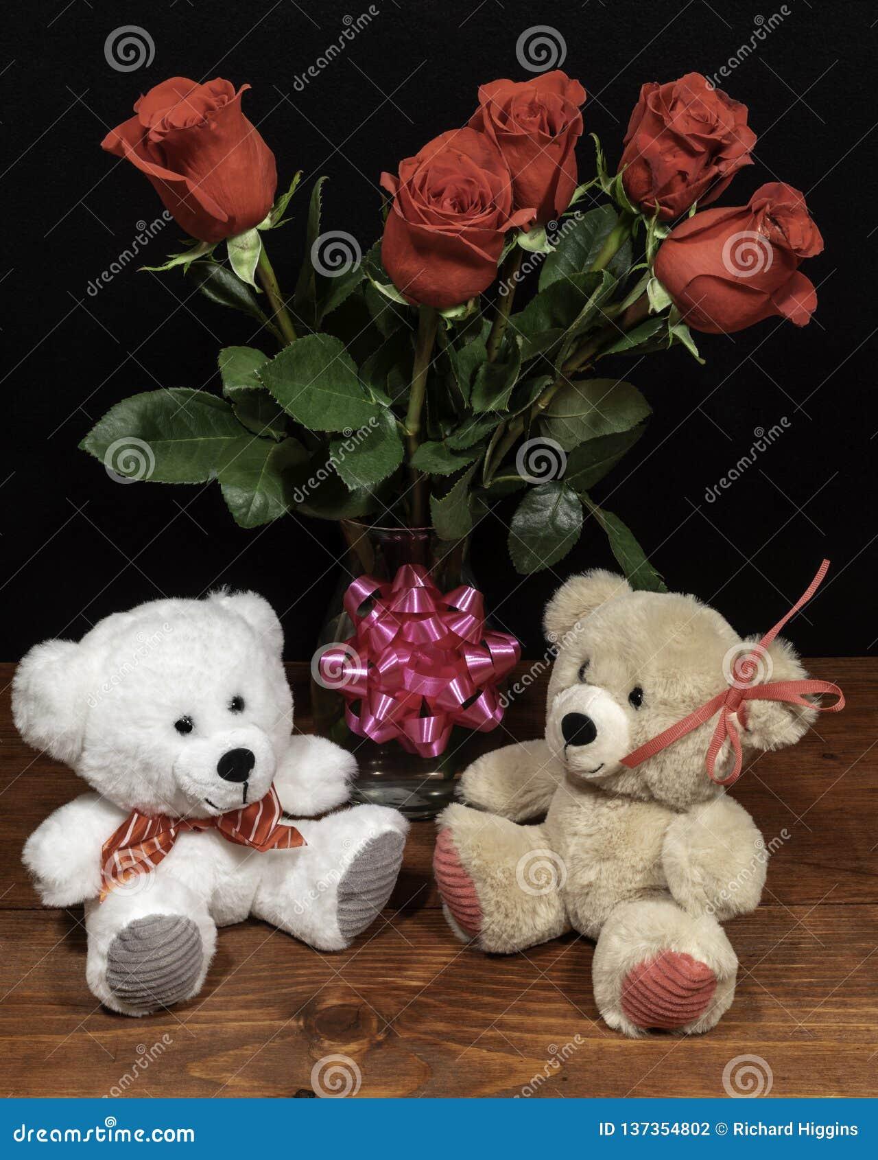Dos osos de peluche mimosos lindos con las rosas rojas en florero y arco rosado en la tabla de madera en fondo oscuro