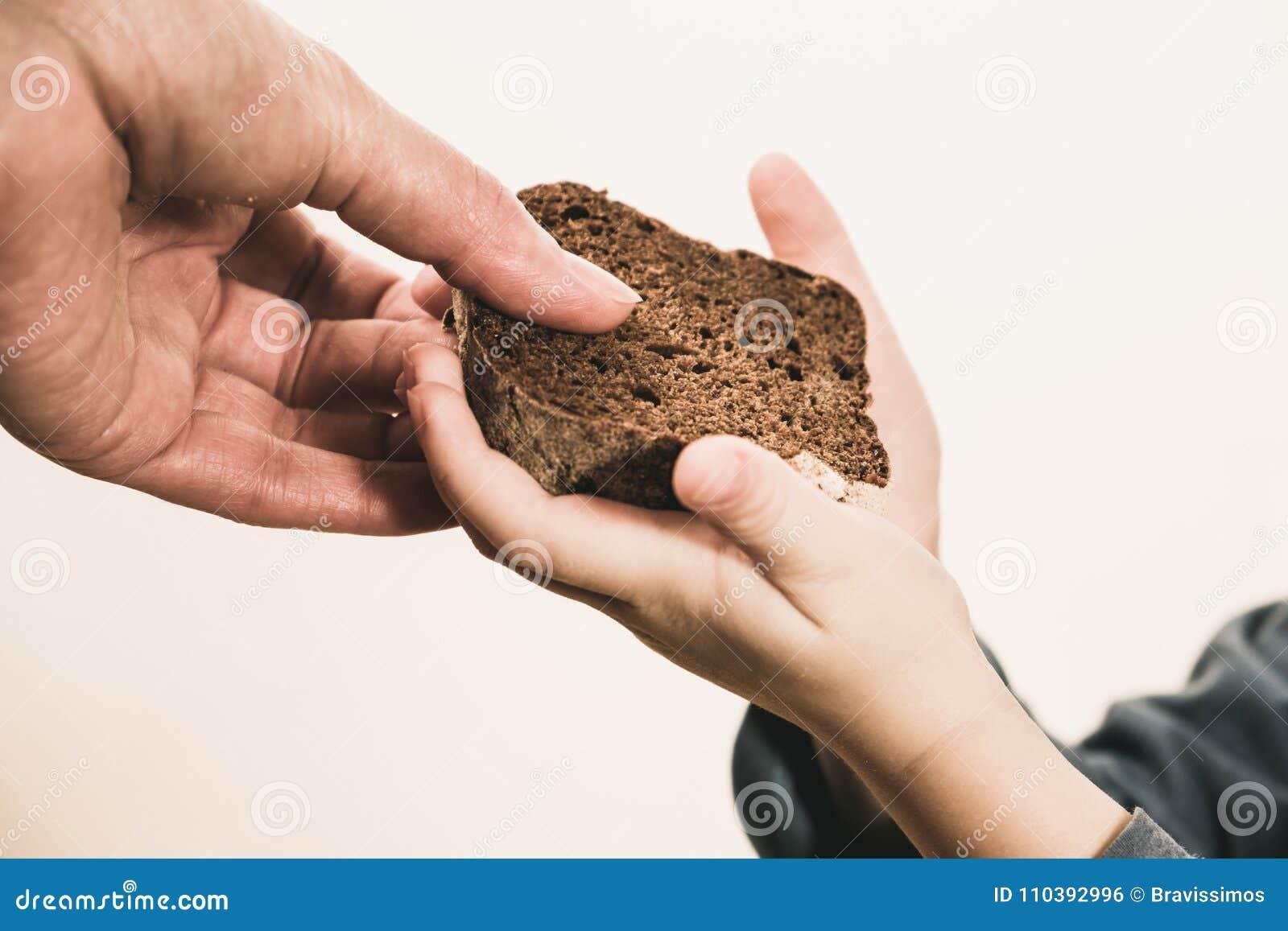 Dos palmas de las manos del mendigo con pan barato Concepto pobre de los voluntarios de las donaciones de los niños y de la gente