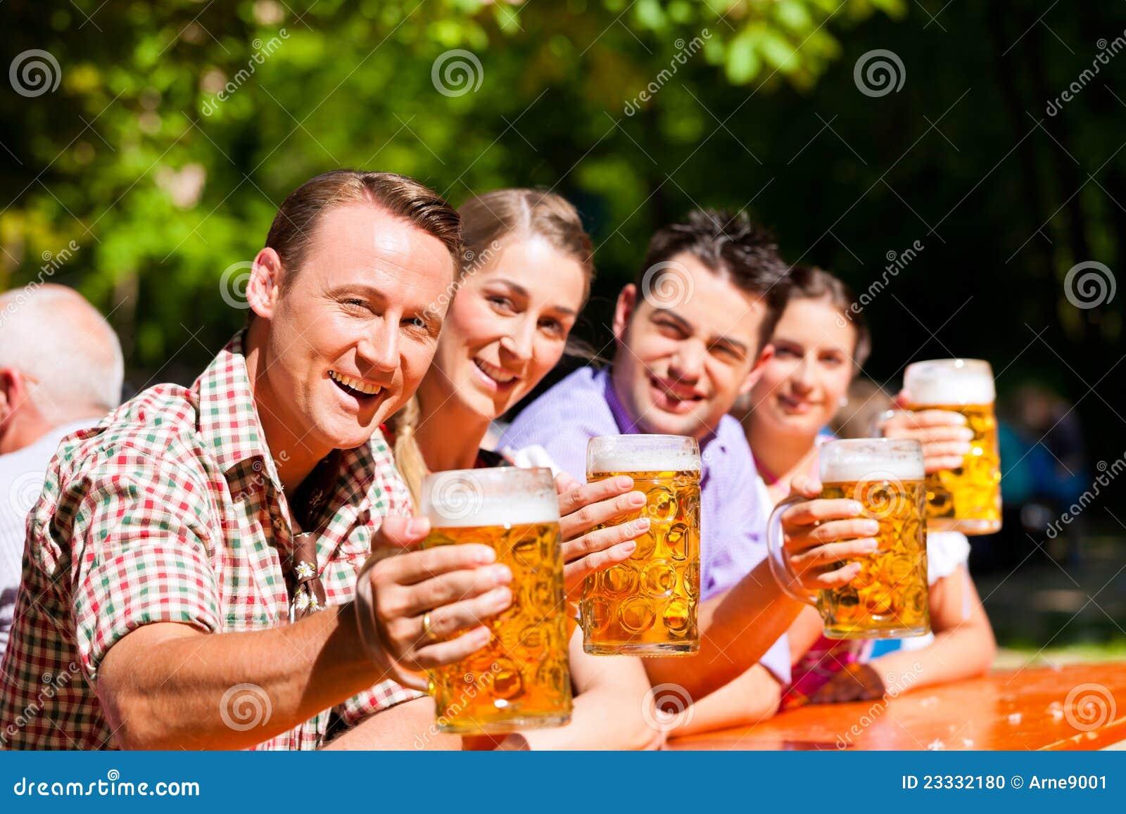 Dos pares felices que se sientan en jardín de la cerveza