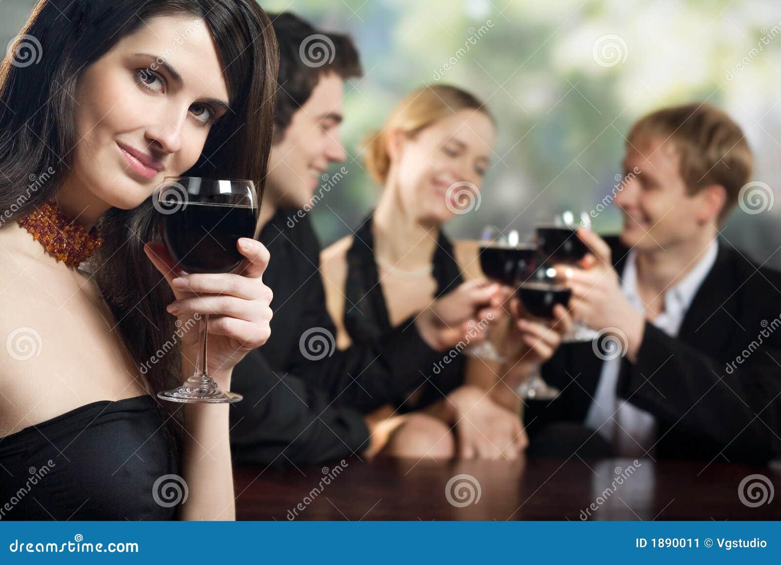 Dos pares jovenes con los vidrios de vino rojo en la celebración o el partido