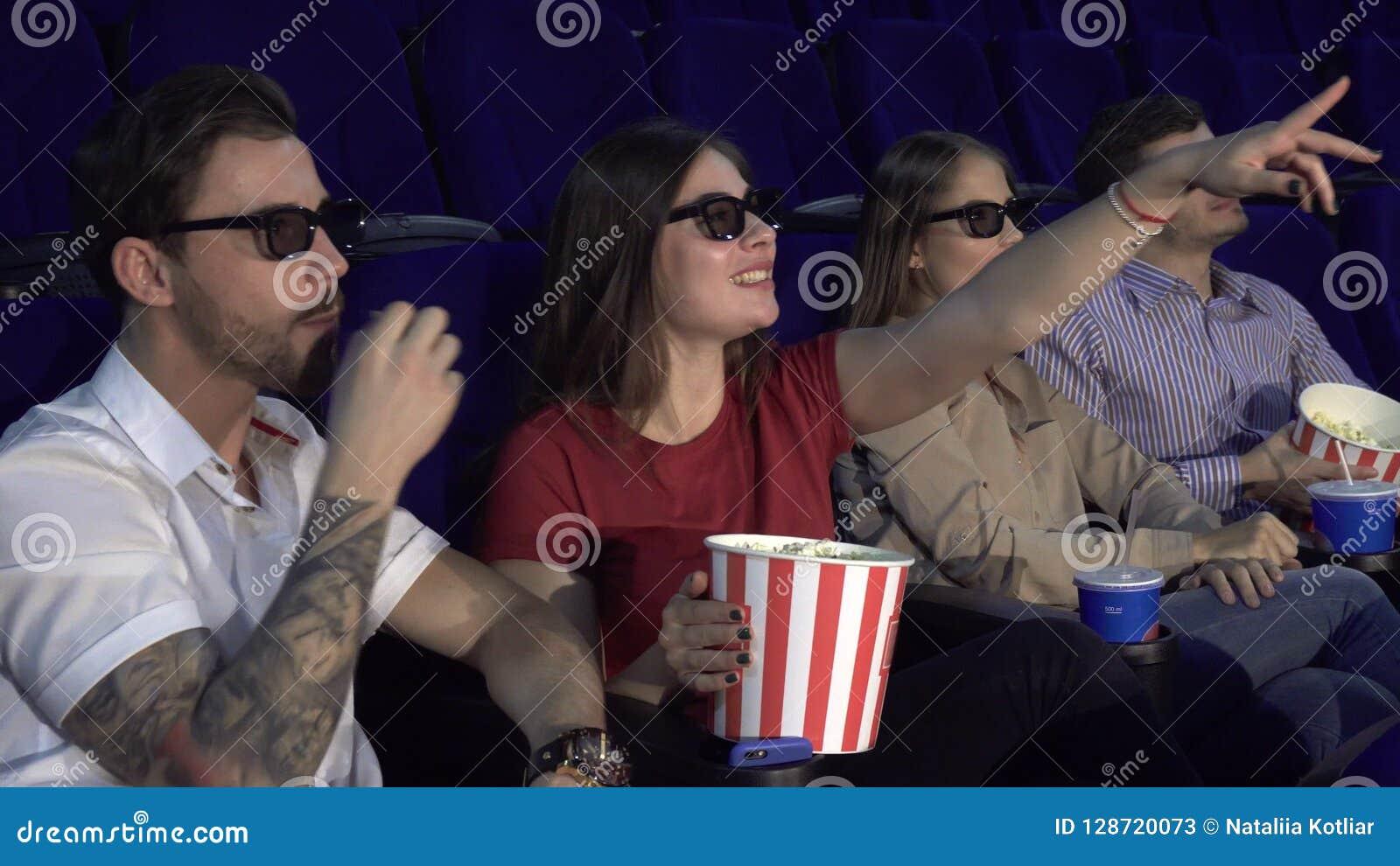 Dos pares se sientan en el cine y comen las palomitas