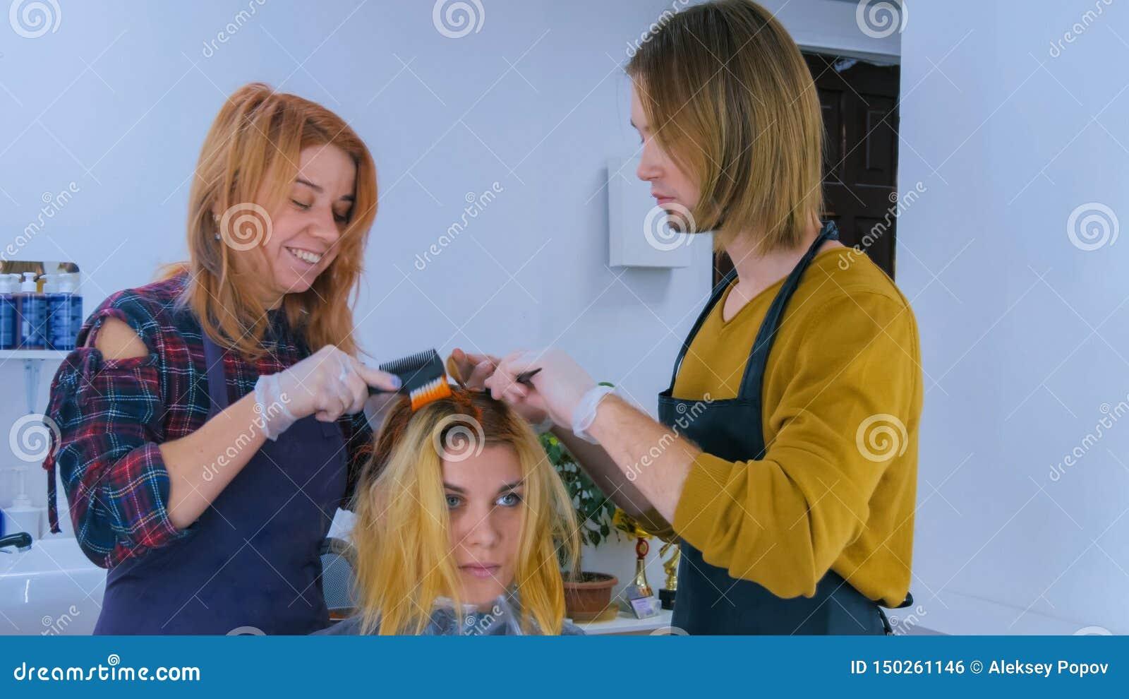 Dos peluqueros profesionales que colorean el pelo del cliente de la mujer en el estudio