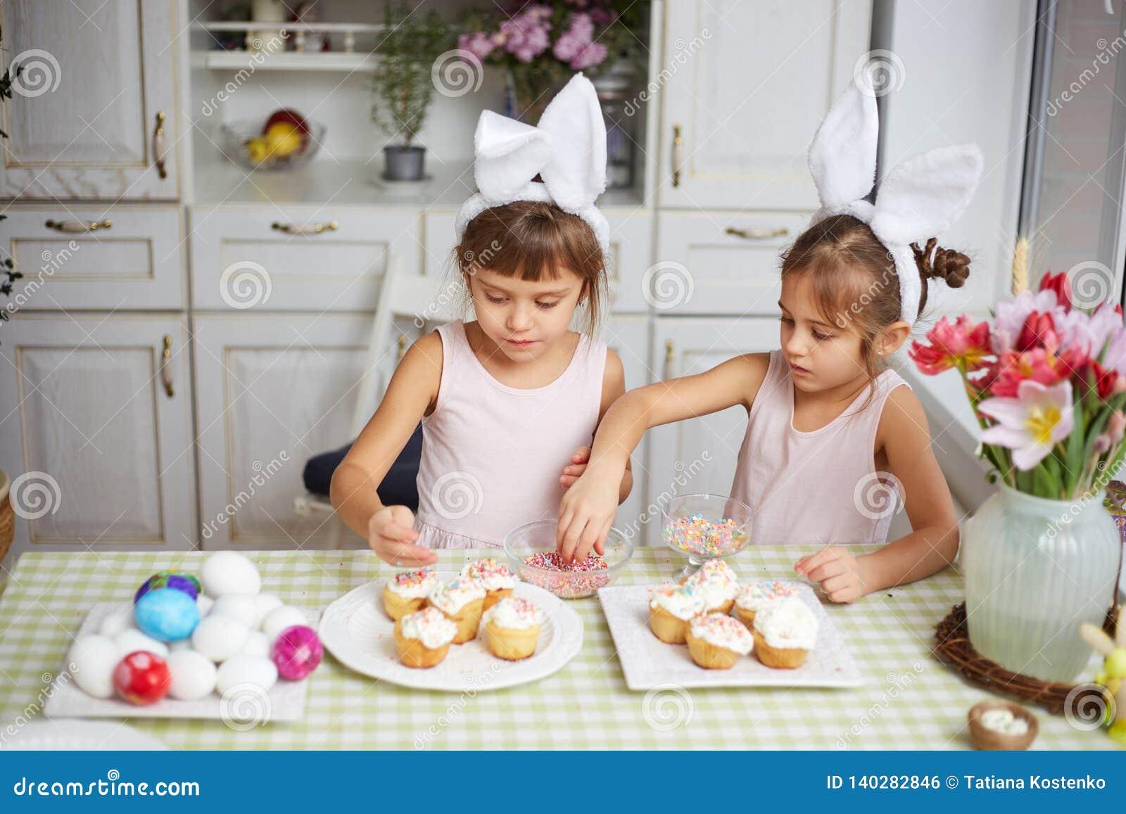 Dos pequeñas hermanas con los oídos de conejo blancos en sus cabezas cocinan las pequeñas tortas de Pascua para la tabla de Pascu