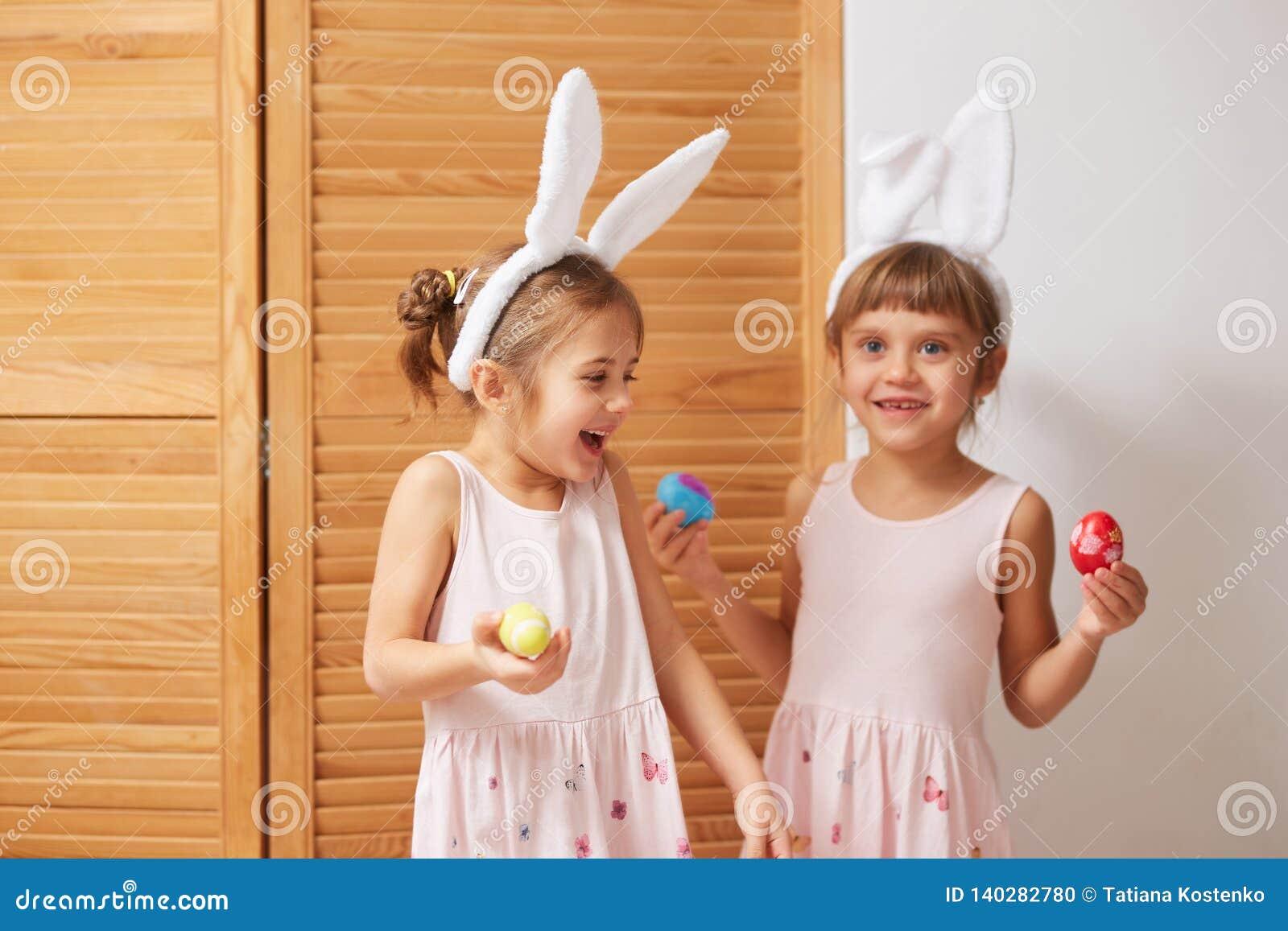 Dos pequeñas hermanas divertidas en los vestidos con los oídos de conejo blancos en sus cabezas se divierten con los huevos teñid