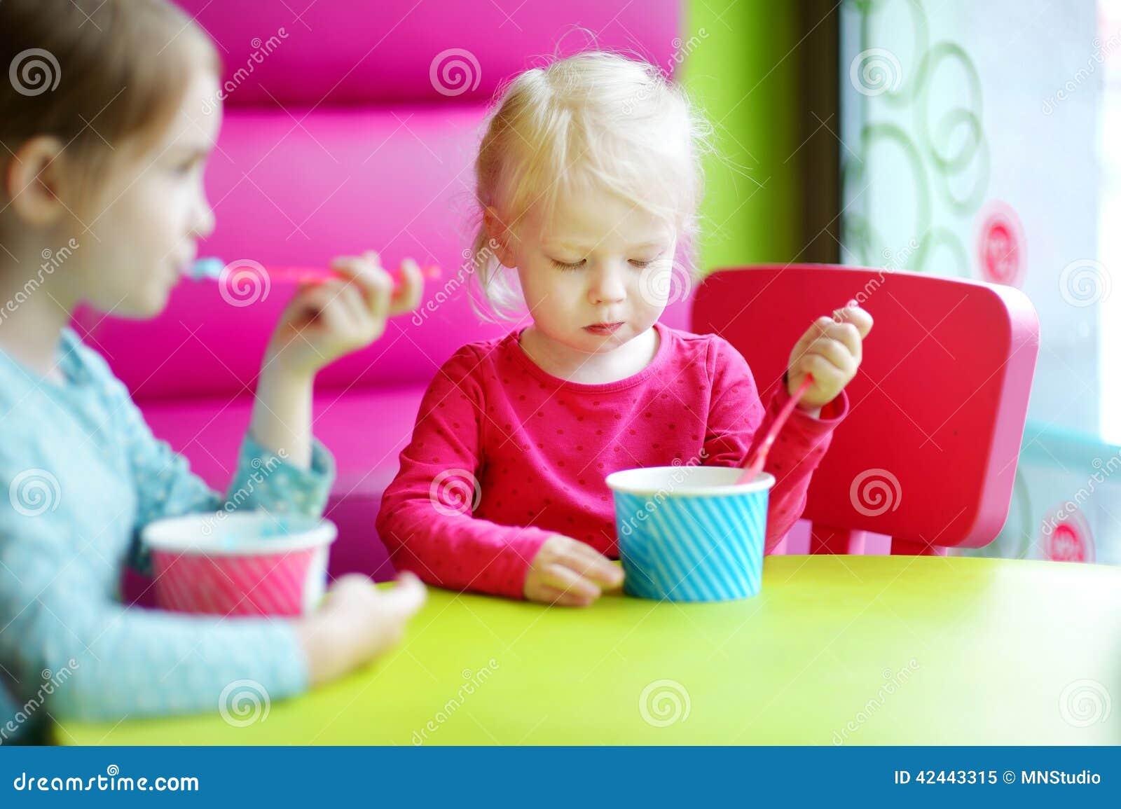 Dos pequeñas hermanas lindas que comen el helado junto