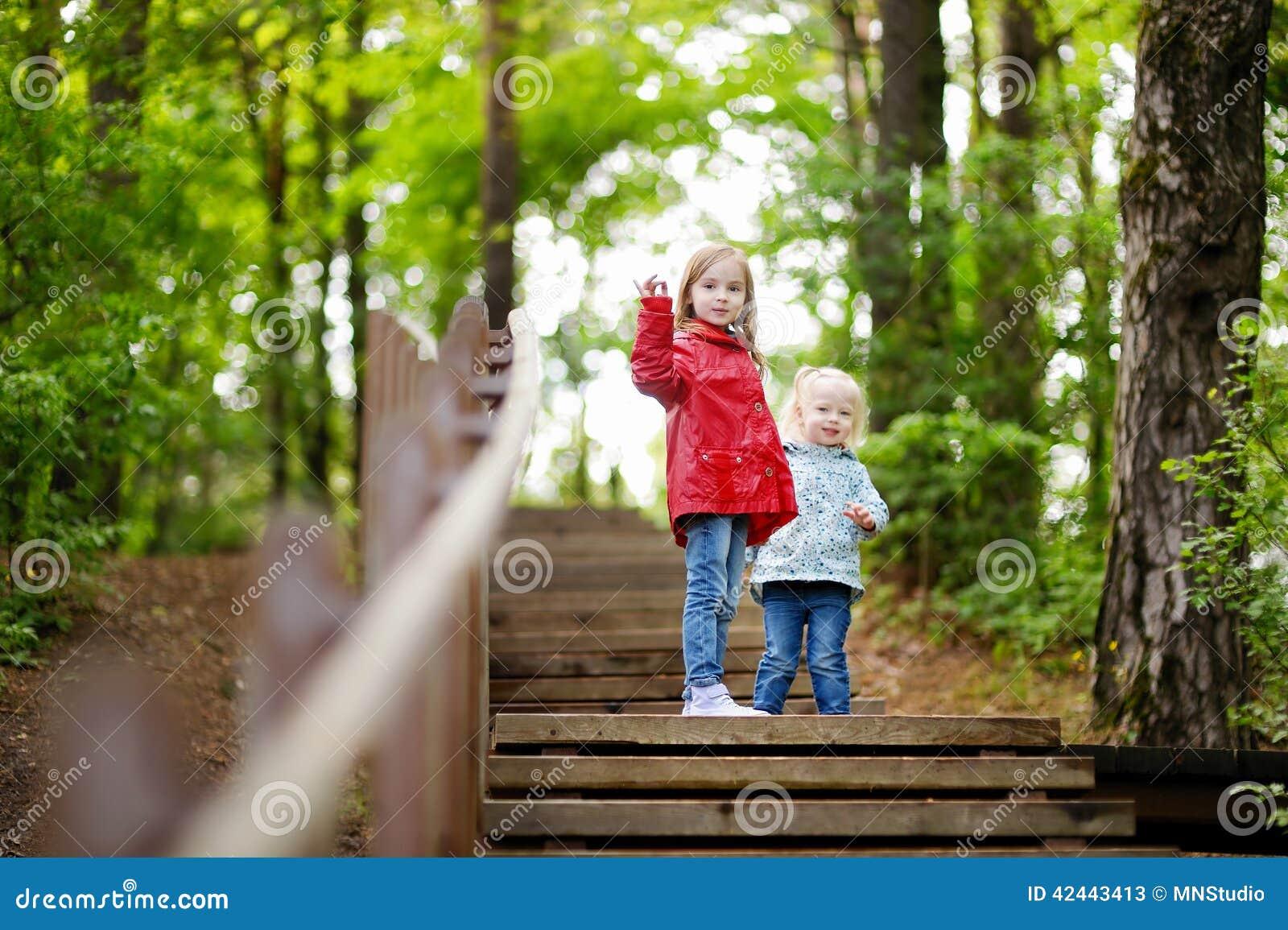 Dos pequeñas hermanas que caminan encima de las escaleras