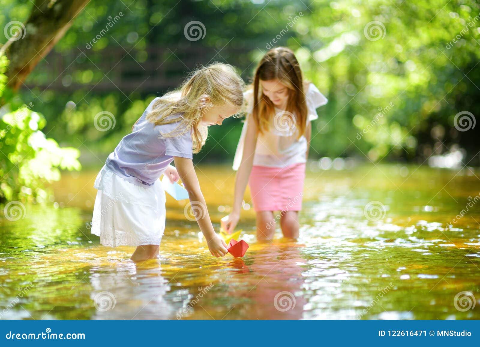 Dos pequeñas hermanas que juegan con los barcos de papel por un río en día de verano caliente y soleado Niños que se divierten po