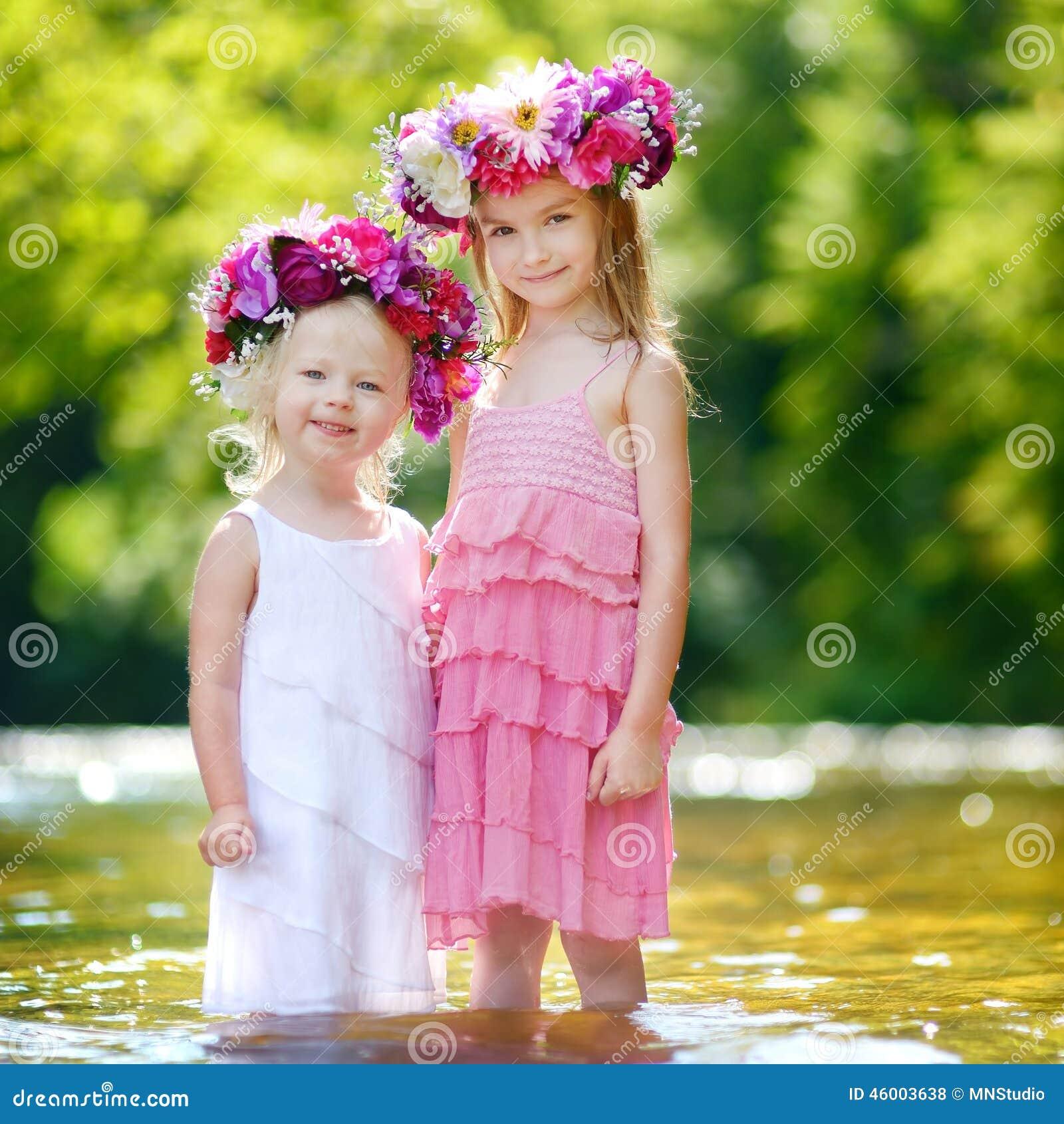 Dos pequeñas hermanas que llevan las coronas de las flores