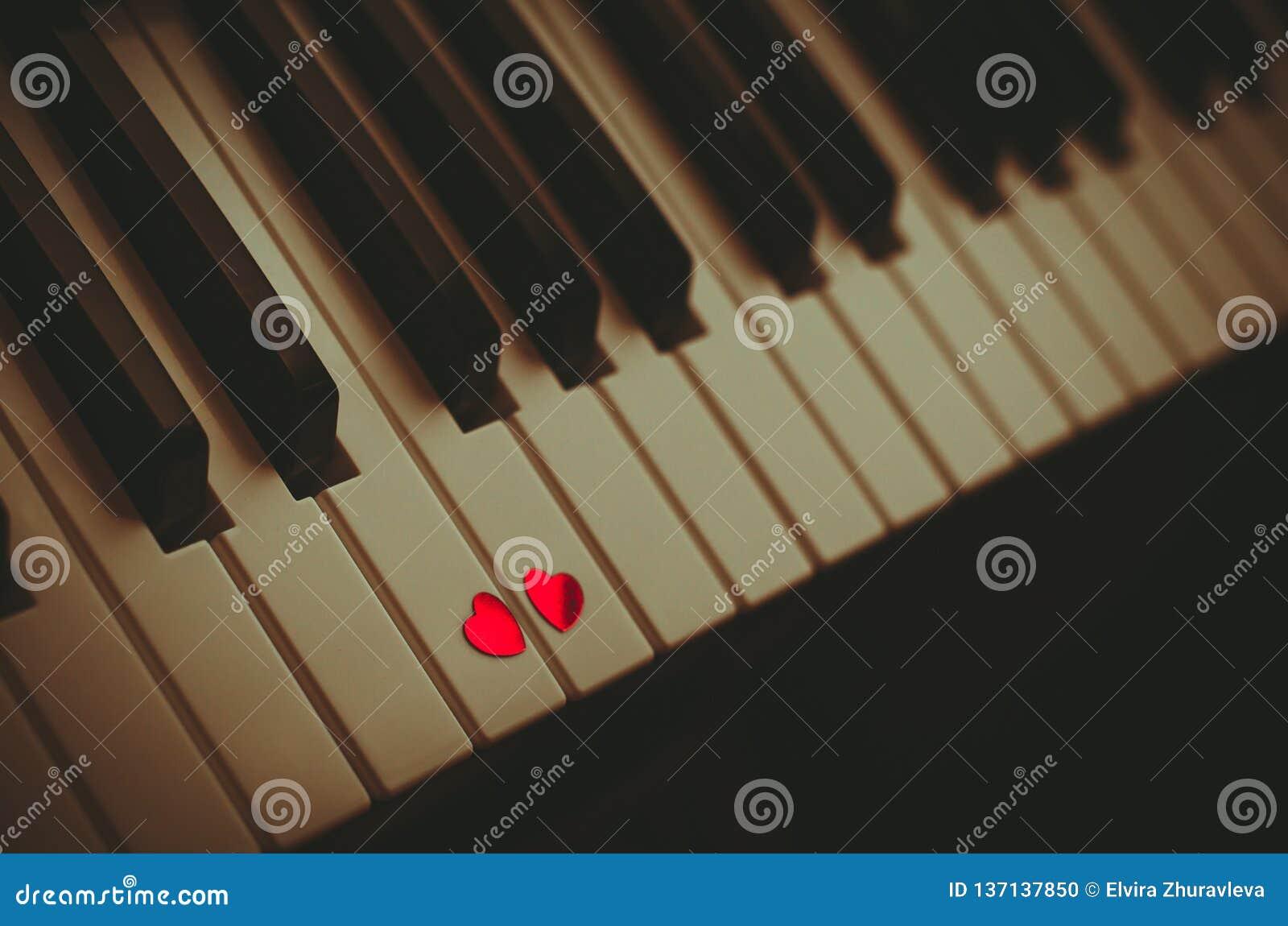 Dos pequeños corazones rojos en el teclado del cierre clásico del piano para arriba Concepto de amor y de música romántica