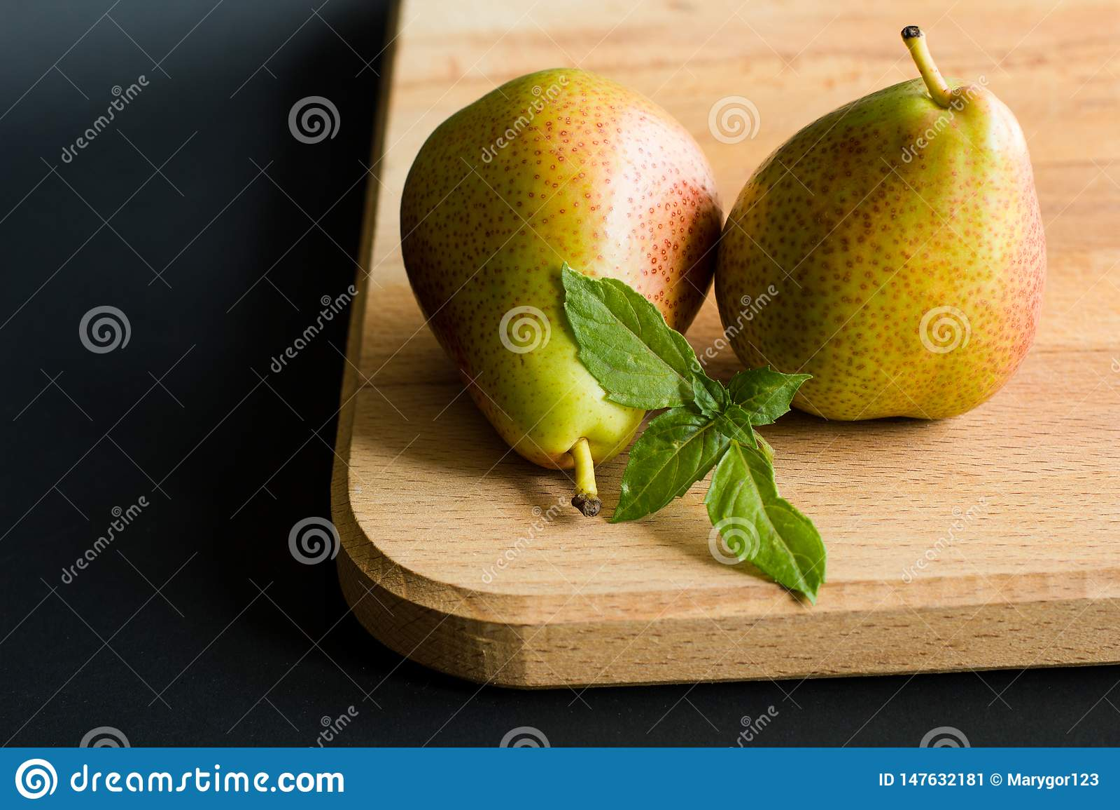 Dos peras con las hojas frescas de la albahaca en una tabla de cortar de madera con el fondo negro