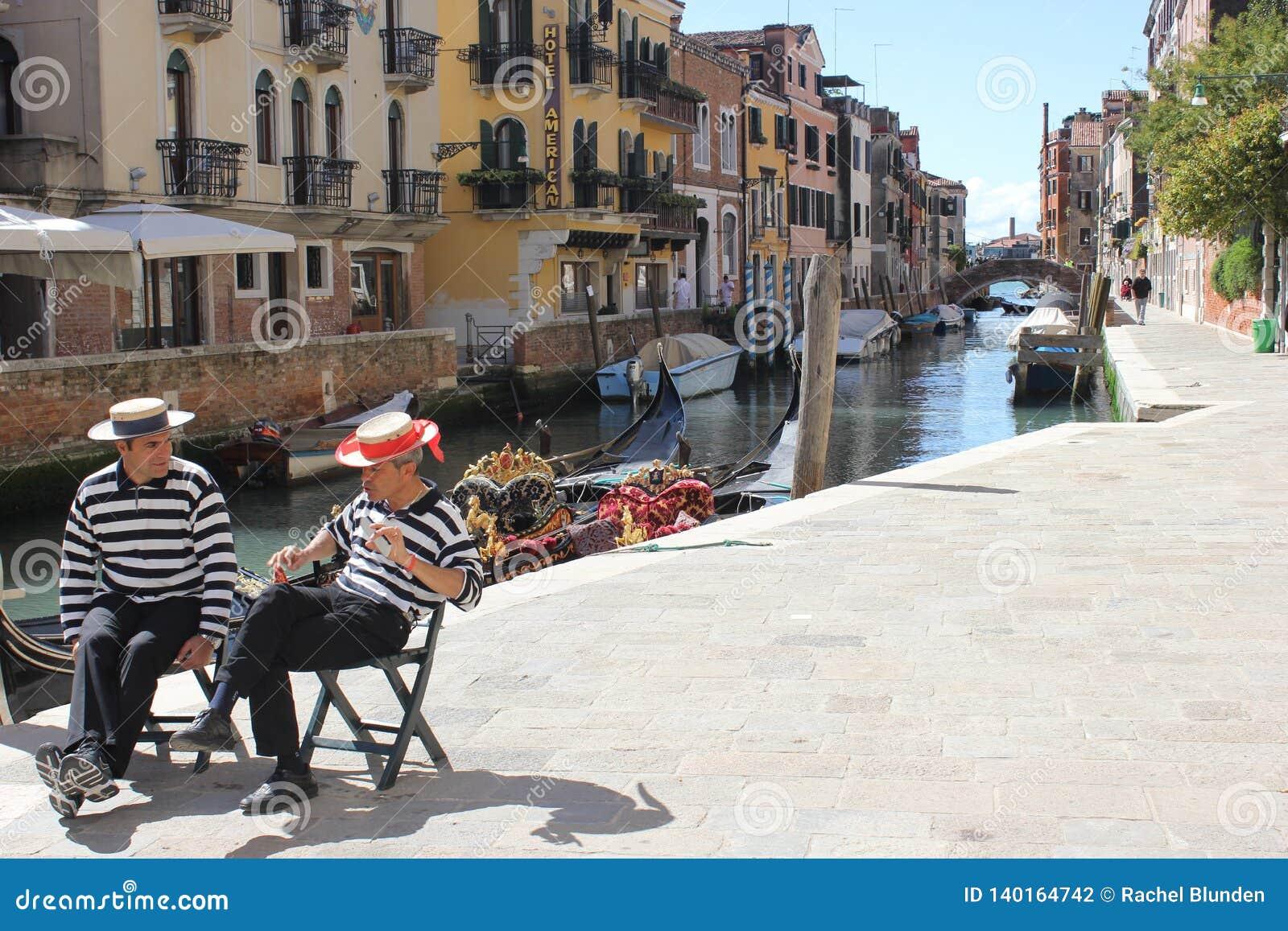 Dos personas de los hombres de la góndola que hablan en el Canal Street de Venecia