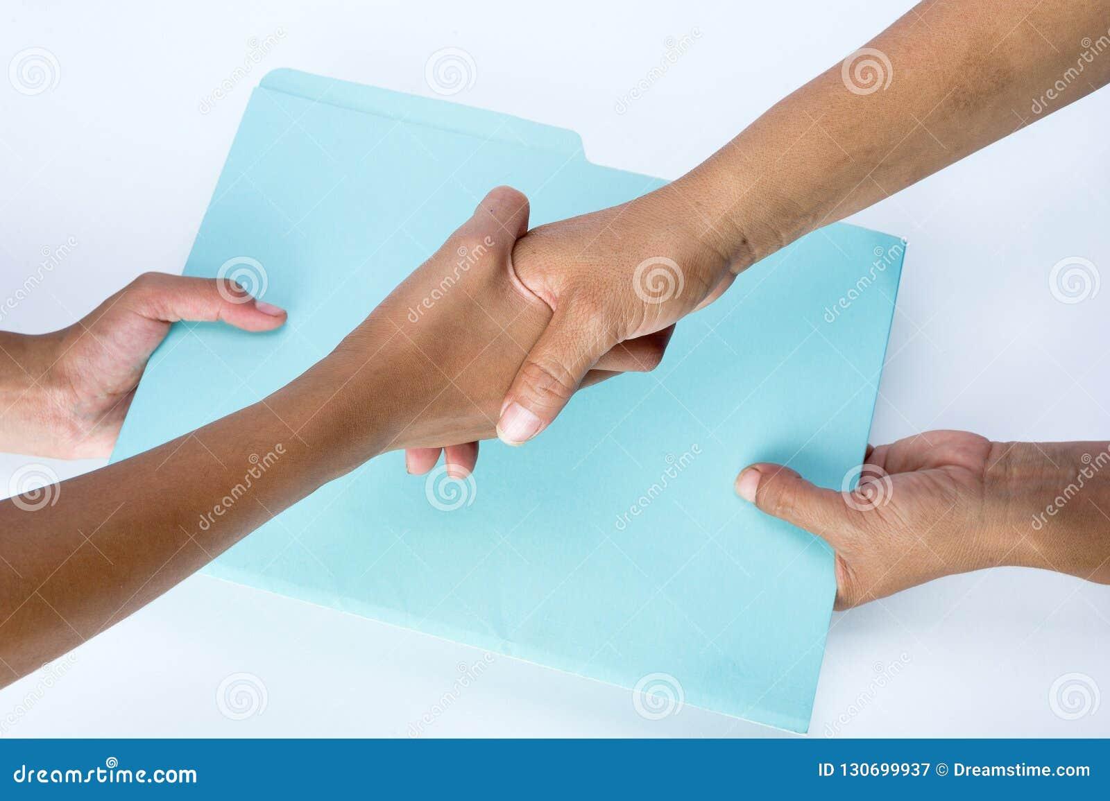 Dos personas que sacuden las manos y que intercambian documentos como muestra del acuerdo