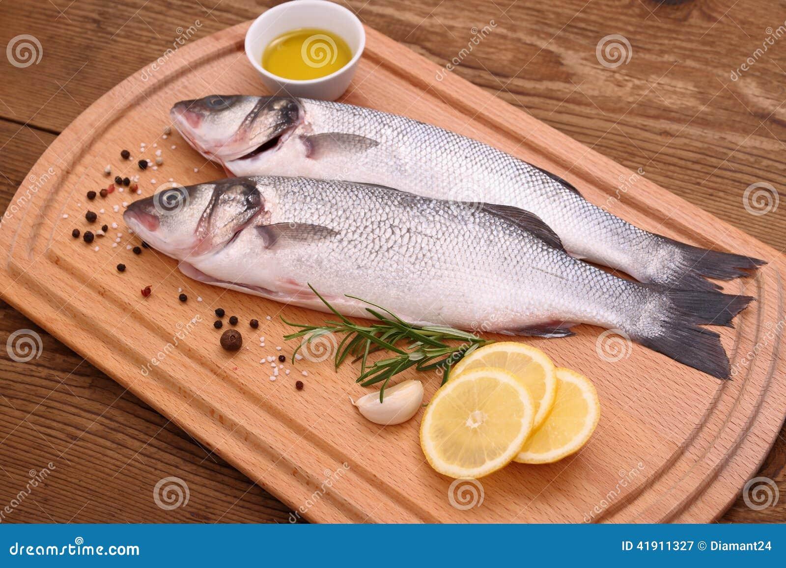 Dos pescados frescos de la lubina en tabla de cortar