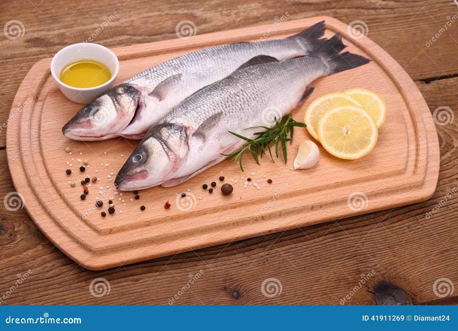 Dos pescados frescos de la lubina en tabla de cortar con el ingr