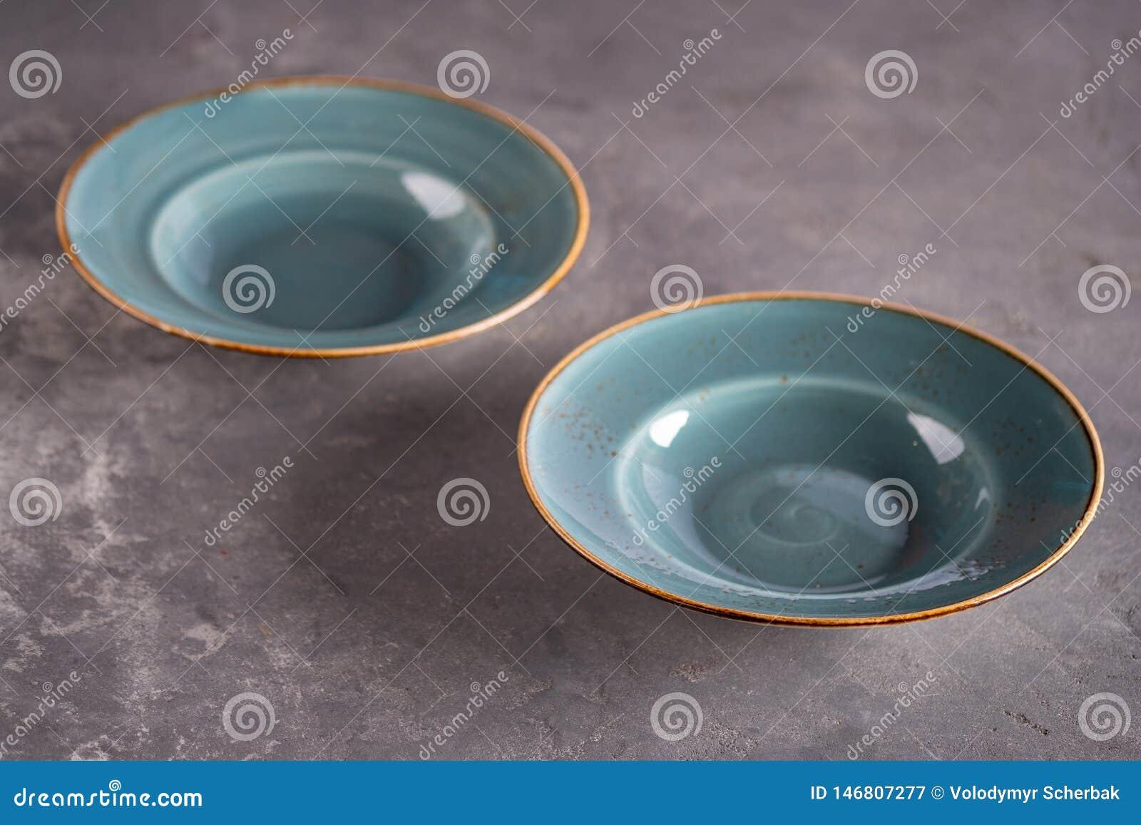 Dos placas vacías azules de la arcilla que permanecen en la tabla