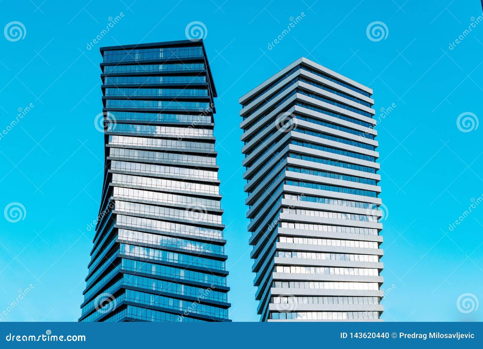 Dos rascacielos altos modernos del negocio con la porción de ventanas de cristal contra el cielo azul - imagen