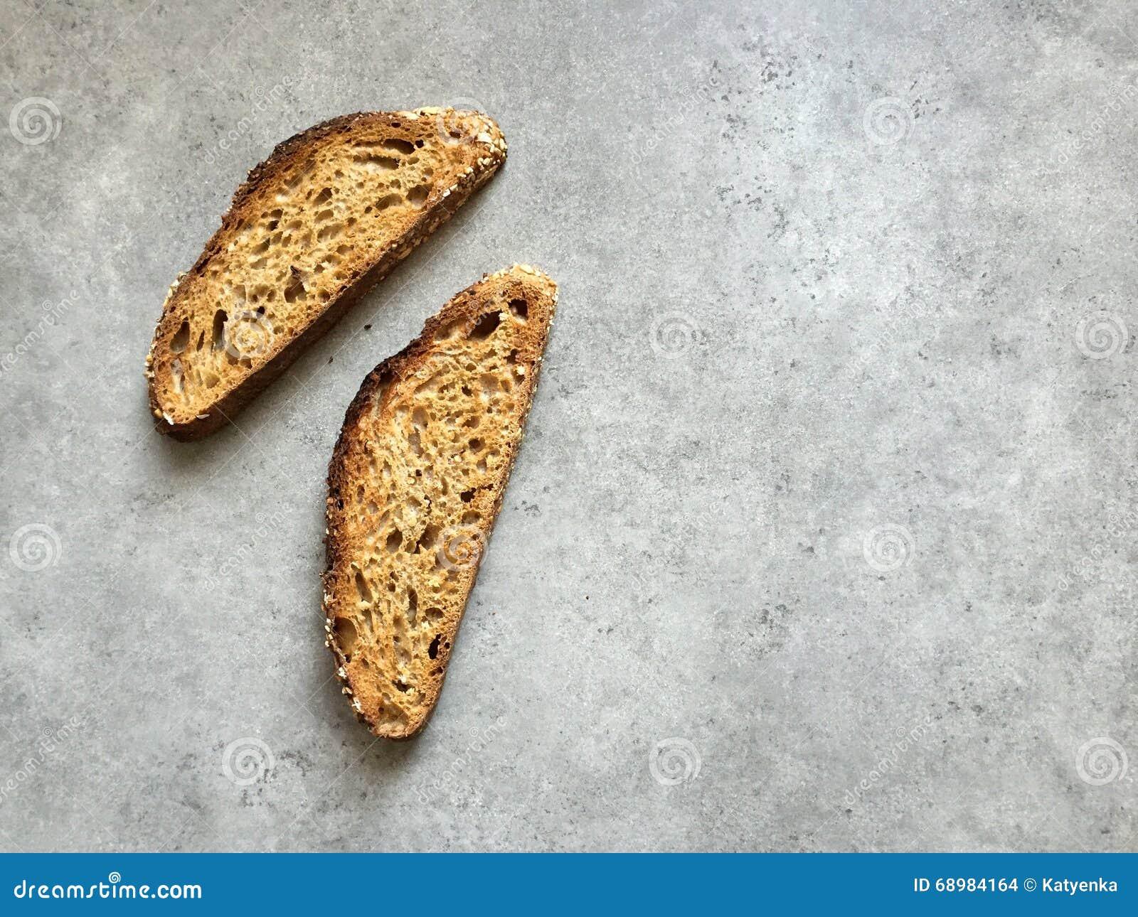 Dos rebanadas de pan artesanal del trigo integral del pan amargo en encimera gris