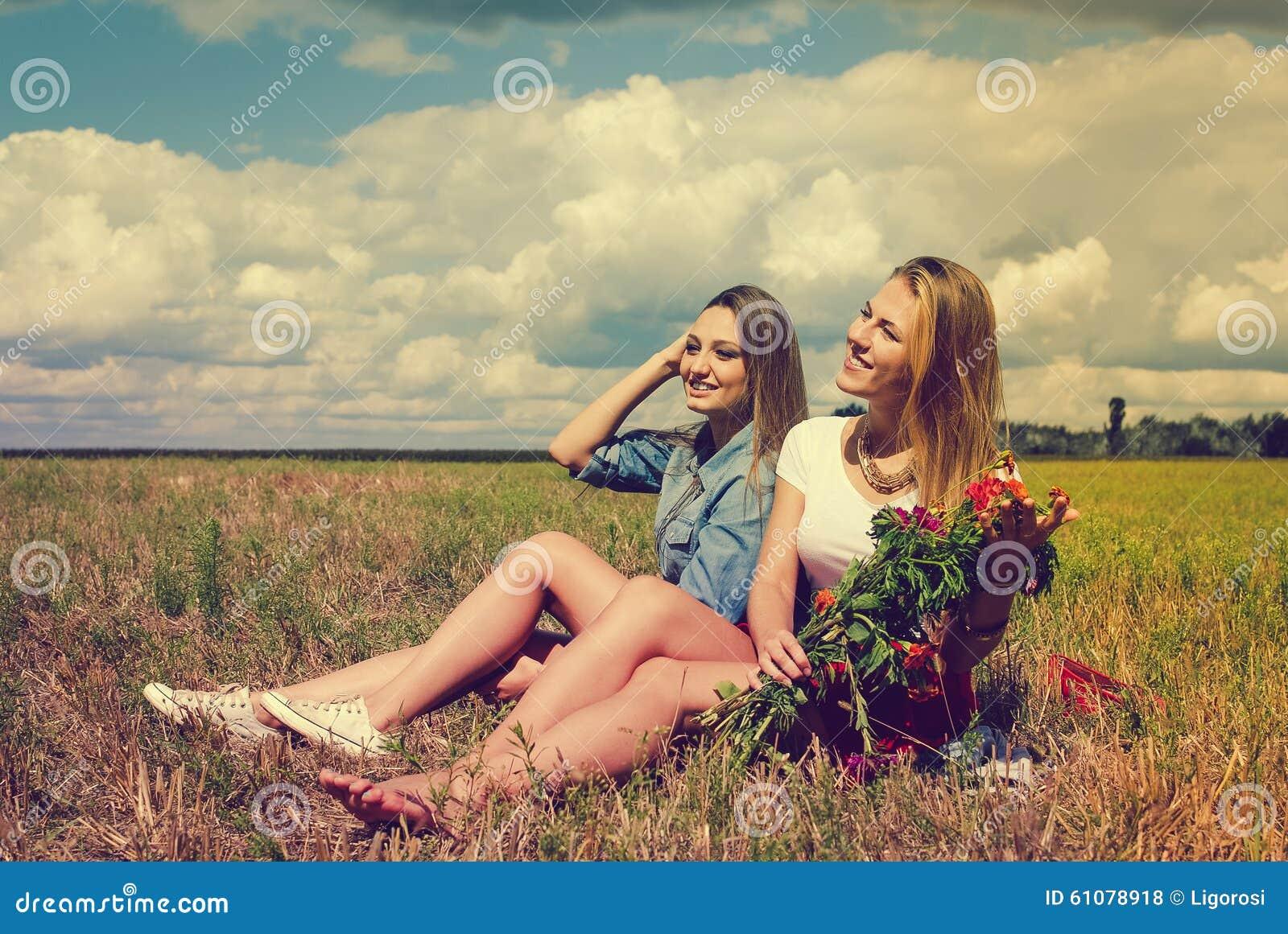 Dos señoras jovenes hermosas que se sientan con las flores encendido