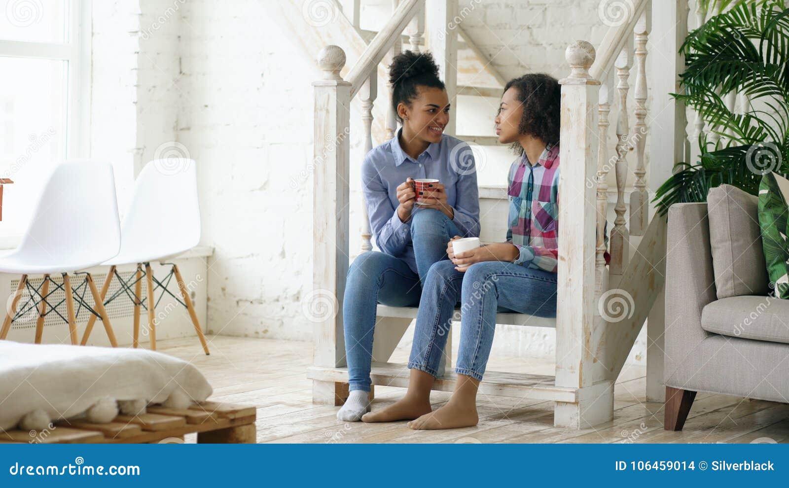 Dos sistres rizados afroamericanos de las muchachas que se sientan en las escaleras se divierten que ríe y que charla juntos en c