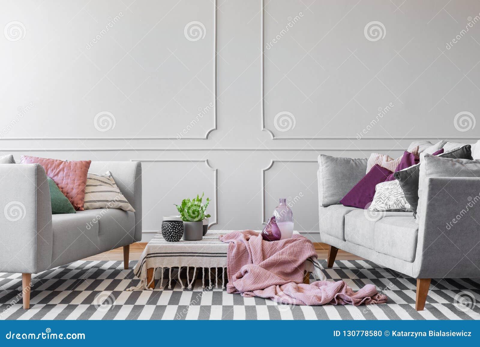 Dos sofás con la porción de almohadas y de mesa de centro con la planta en pote, los floreros de cristal y las tazas de café en l
