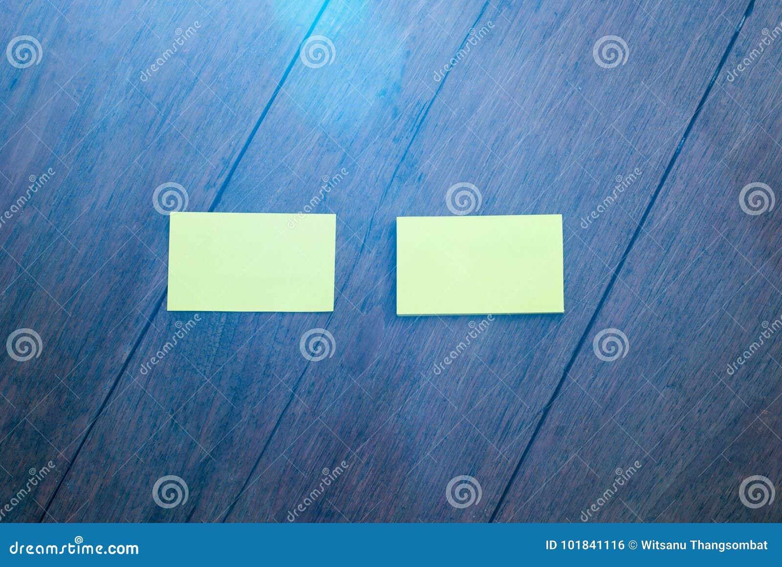 Dos tarjetas de visita verticales en blanco blancas en de madera natural ligero