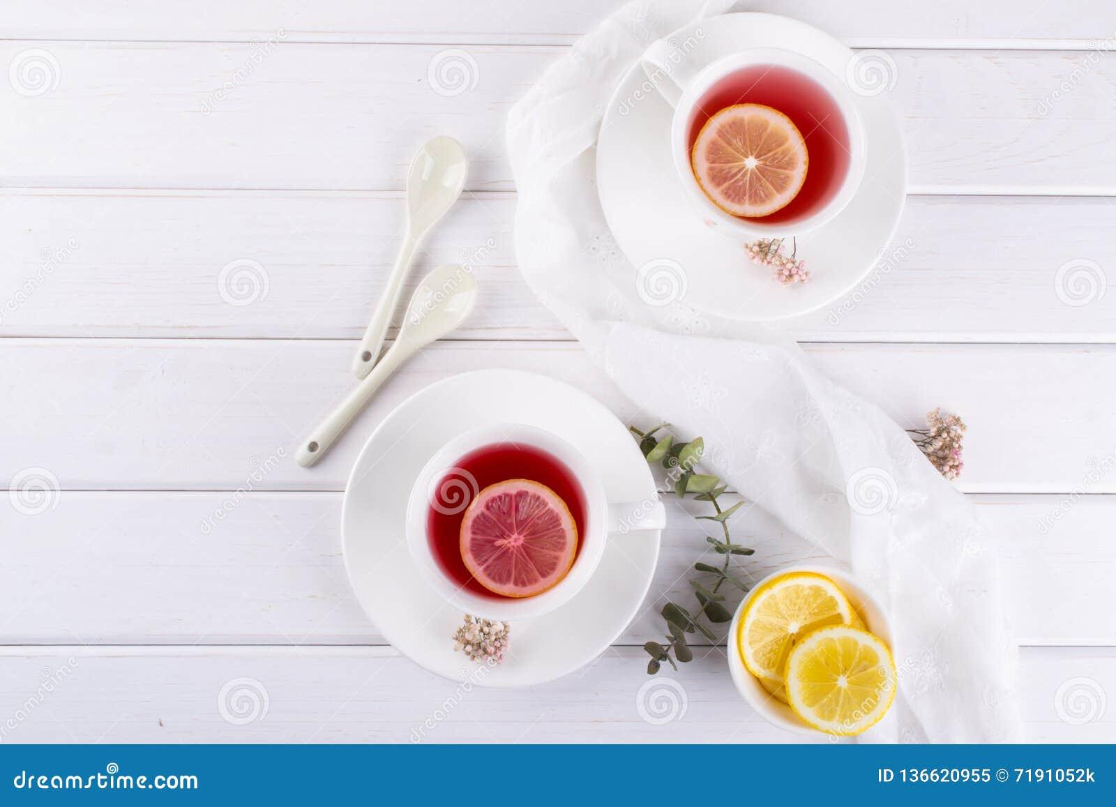 Dos tazas de fruta y de infusión de hierbas rojas con la rebanada del limón
