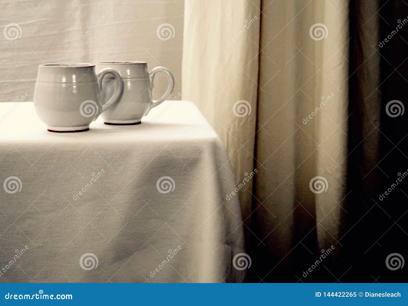 Dos tazas de té blancas en una tabla blanca contra un fondo blanco