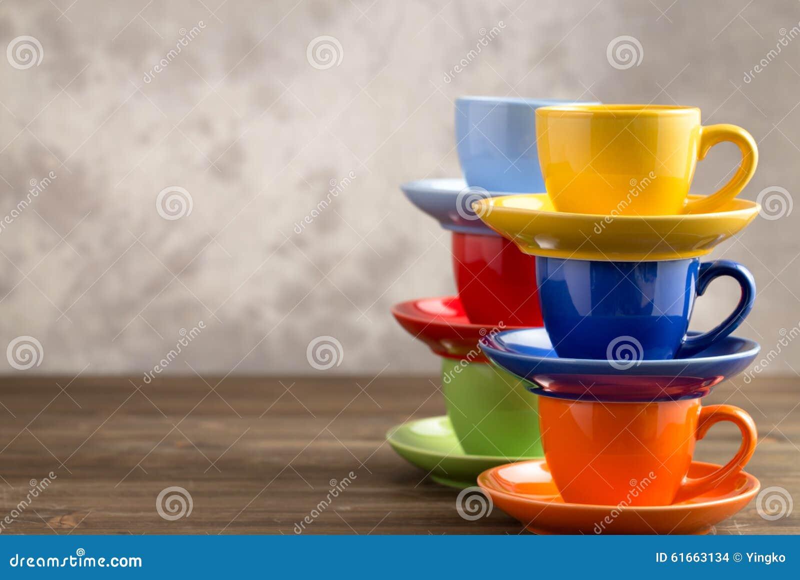 Dos tazas multicoloras de las pilas en la tabla del lado derecho
