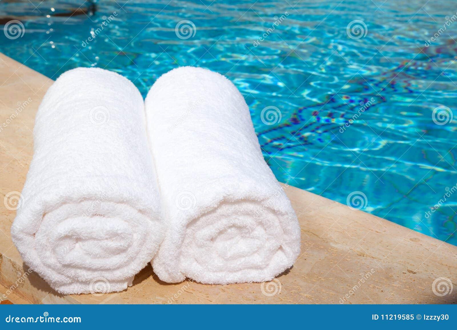 Dos toallas blancas enrolladas por la piscina azul foto de for Toallas piscina