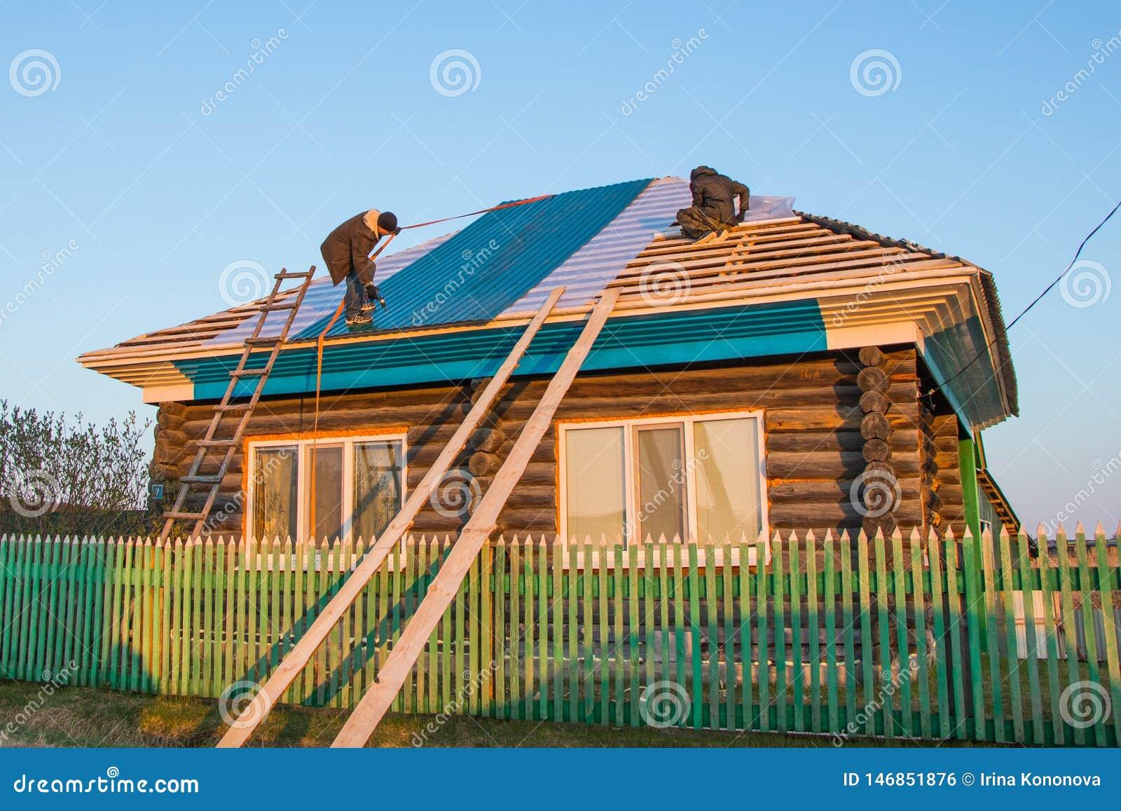 Dos trabajadores cubren el tejado de una casa rural con las tejas del metal