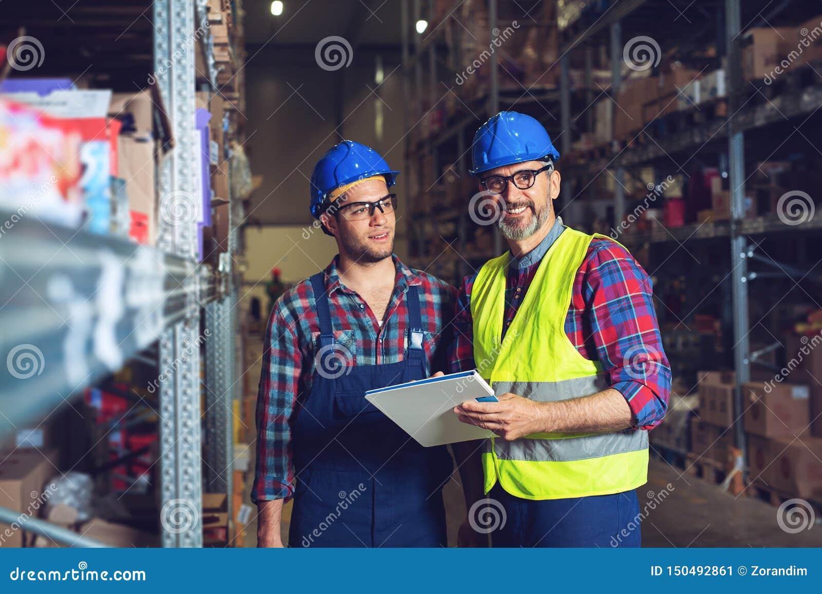 Dos trabajadores del almac?n que completan el documento