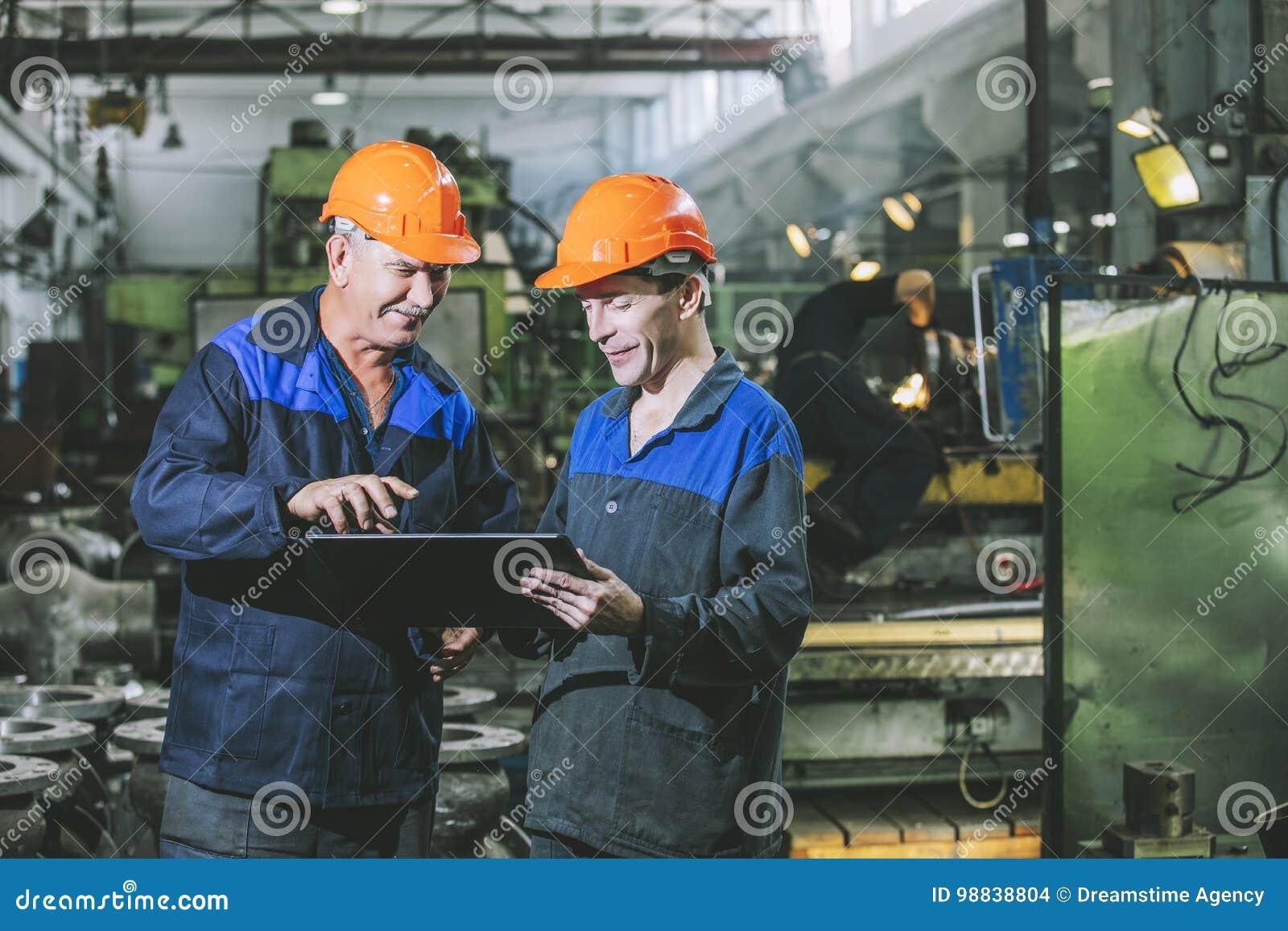 Dos trabajadores en una planta industrial con una tableta a disposición, workin
