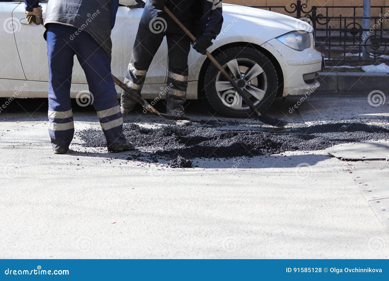 Dos trabajadores están nivelando la miga del asfalto en el hoyo con un fricción-rodillo antes de pavimentar con un mini rodillo d