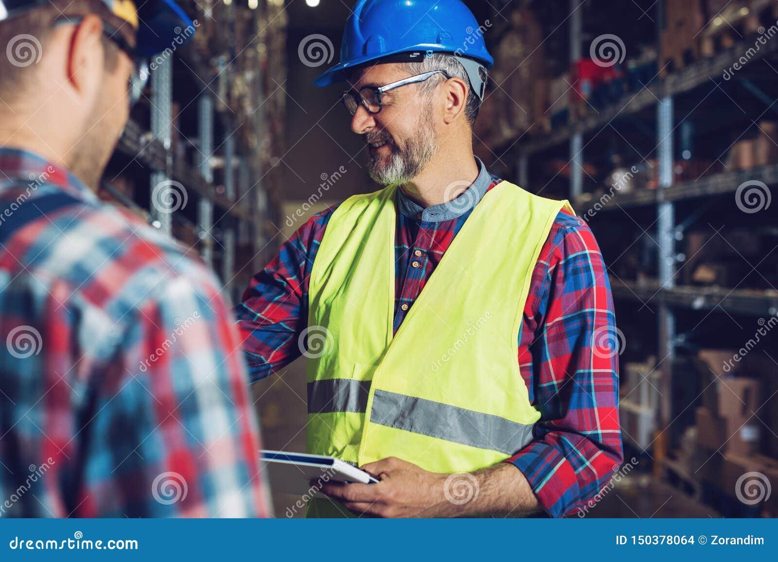 Dos trabajadores jovenes en uniformes en almacén