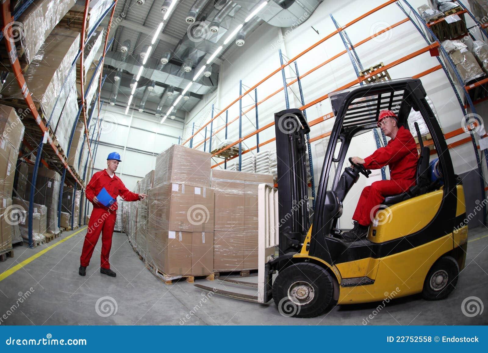 Dos trabajadores que recargan las paletas con tru de la carretilla elevadora