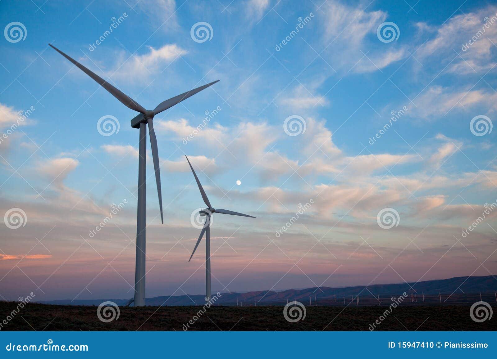Dos turbinas de viento en la puesta del sol con la luna