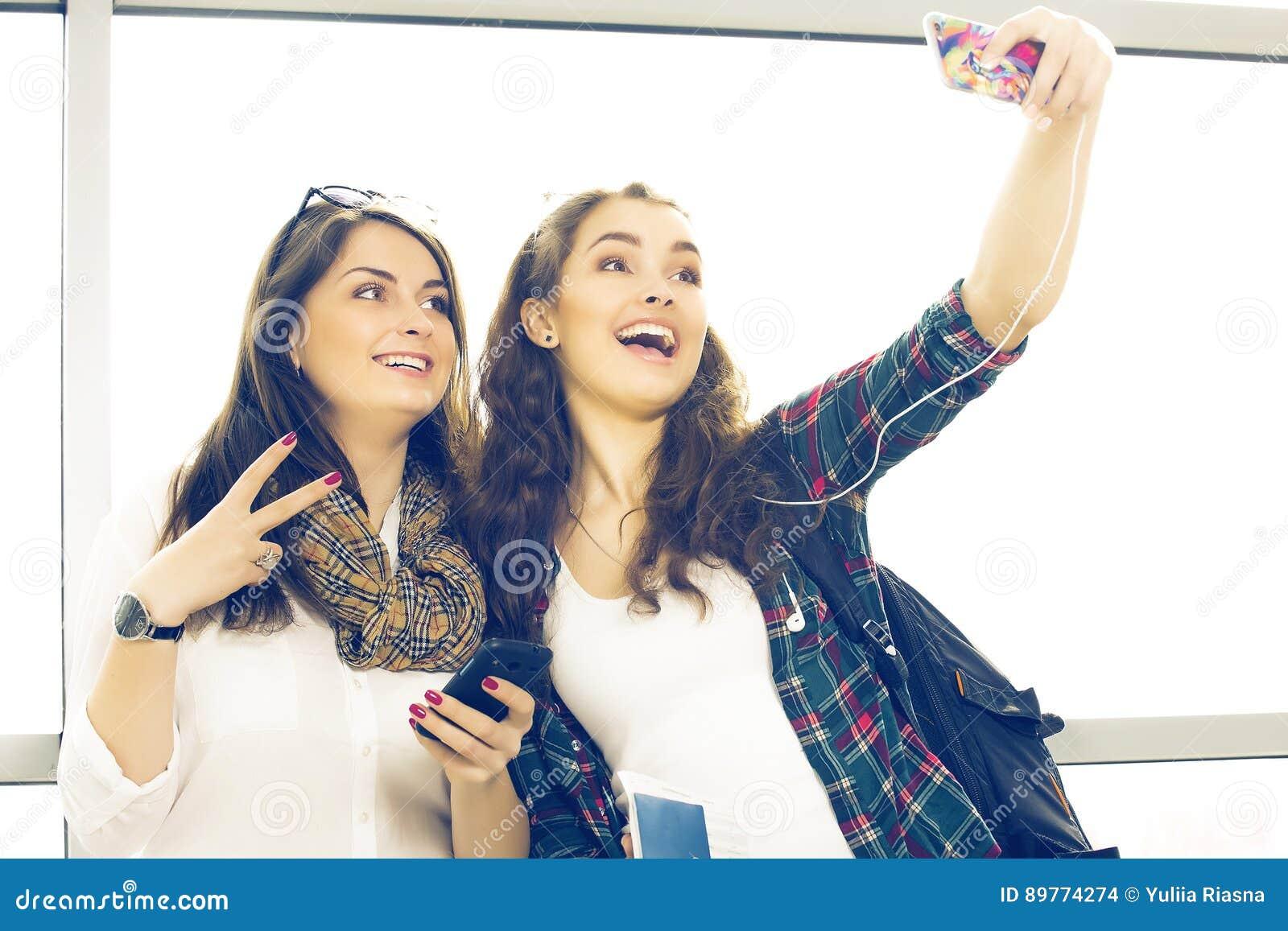 Dos turistas de las mujeres jovenes que sostienen un pasaporte y hacen el terminal del selfie