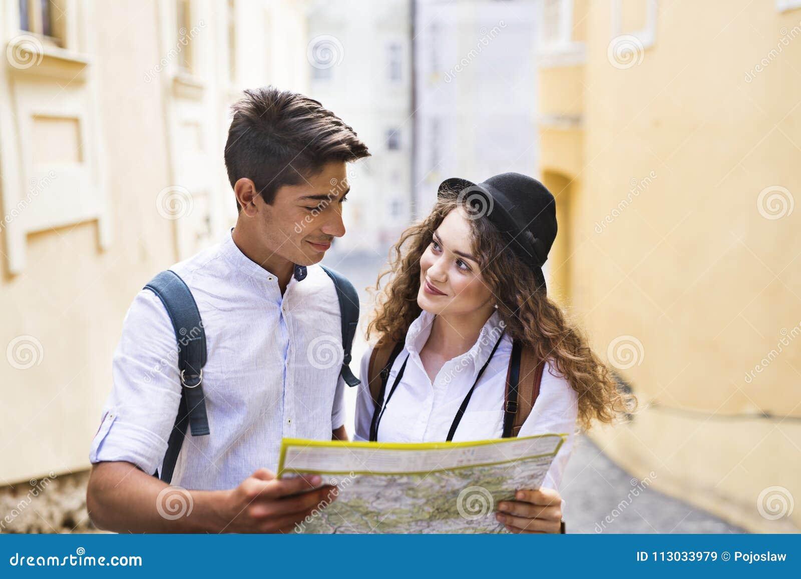 Dos turistas jovenes con el mapa y la cámara en la ciudad vieja