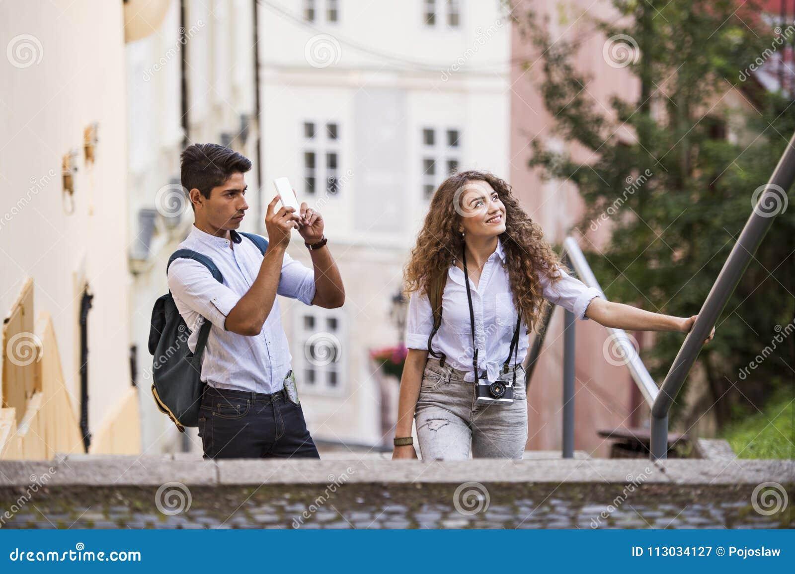 Dos turistas jovenes con smartphone y la cámara