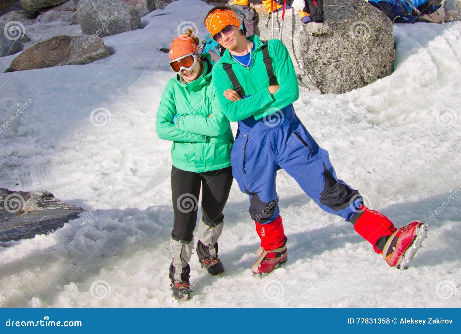 Dos turistas mujer y hombre de los escaladores de hielo que presentan en el mismo paño
