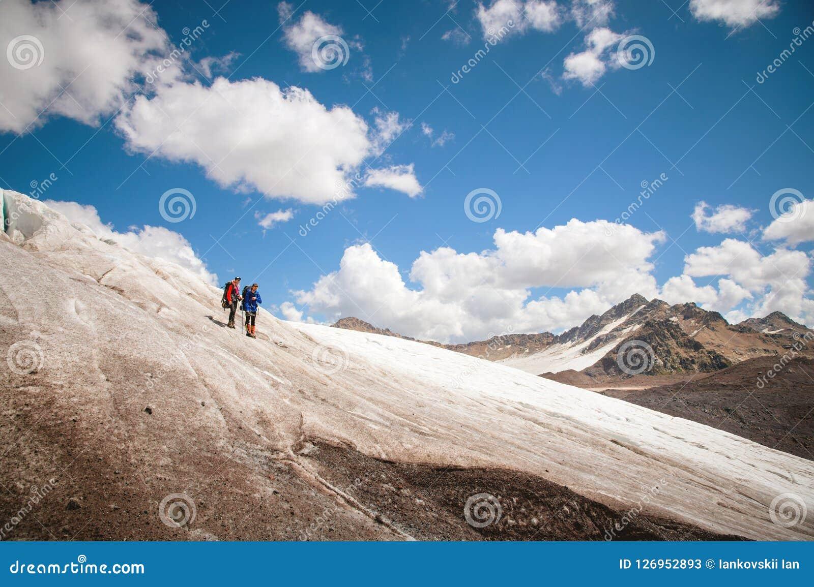 Dos turistas, un hombre y una mujer con las mochilas y los gatos en sus pies, soporte en el hielo en el fondo del