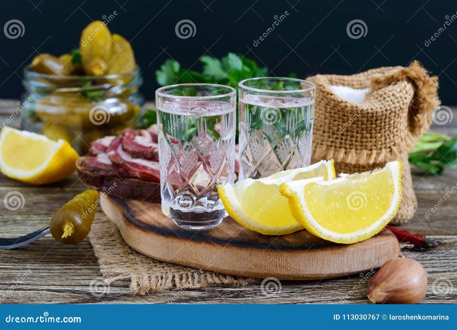 Dos vasos de medida de vodka con el limón cortan, conservaron en vinagre los pepinos y el pan de centeno con tocino salado