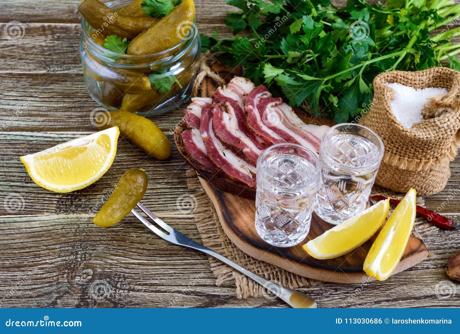 Dos vasos de medida de vodka con el limón cortan, conservaron en vinagre los pepinos y el pan de centeno con tocino salado en el