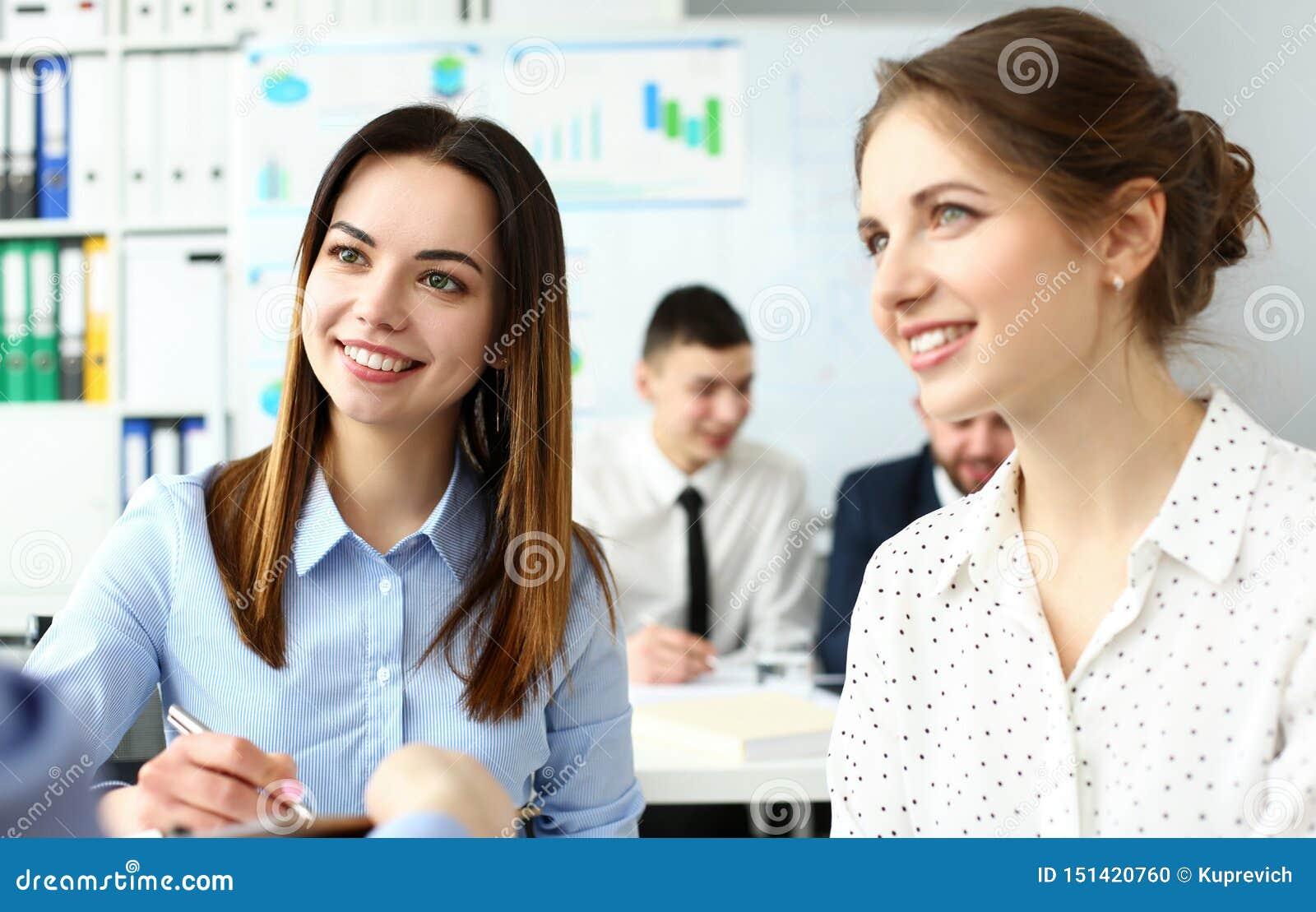 Dos vendedores femeninos caucásicos hermosos sonrientes que discuten en oficina algunos problemas de negocio