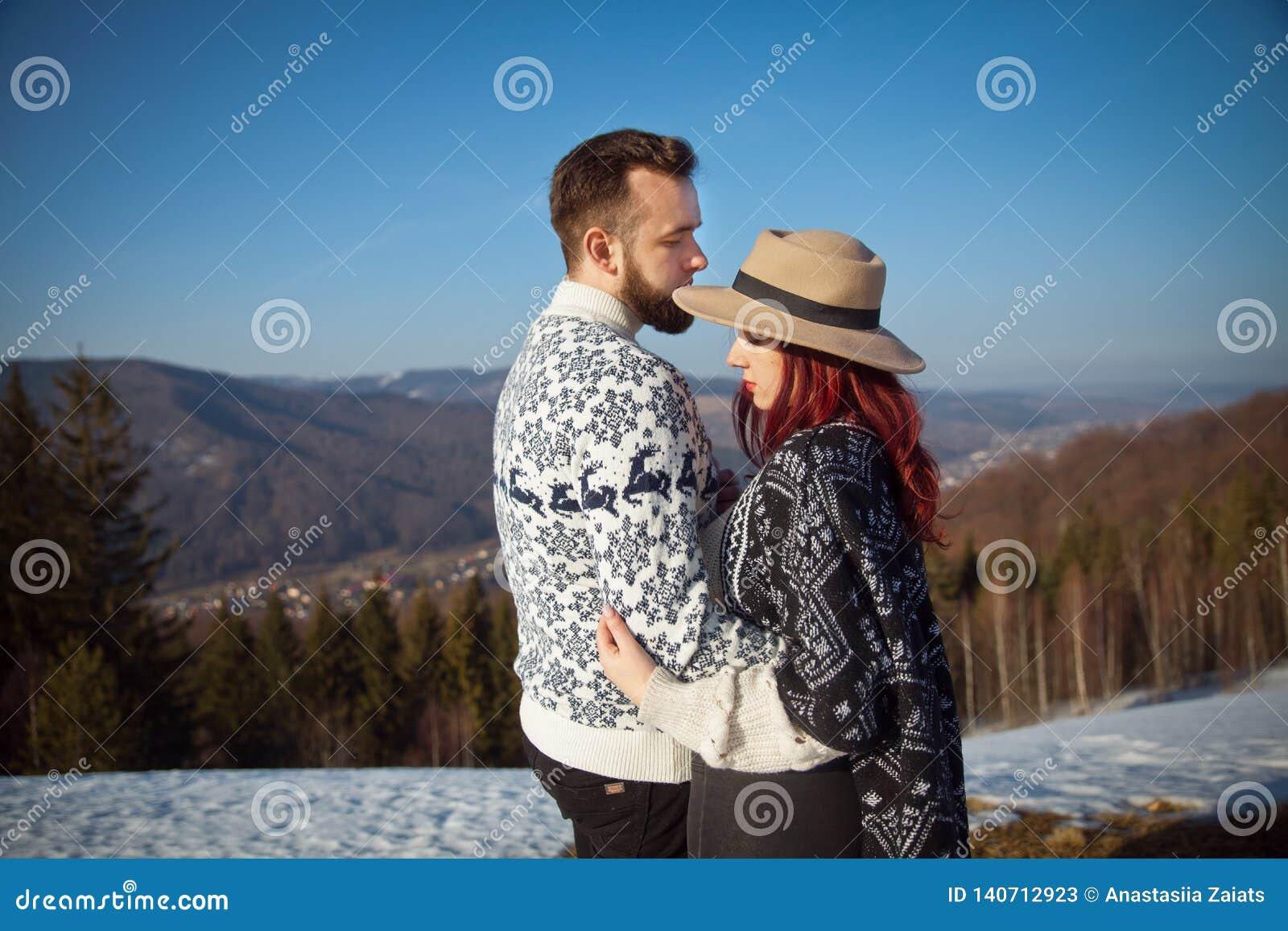 Dos viajeros jovenes que abrazan en las montañas