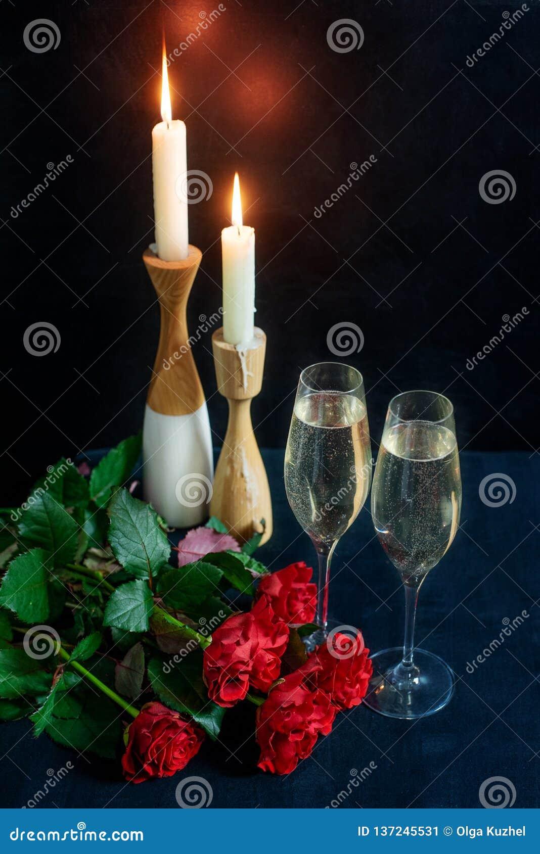 Dos vidrios con el champán blanco y un ramo de rosas rojas en el fondo de velas