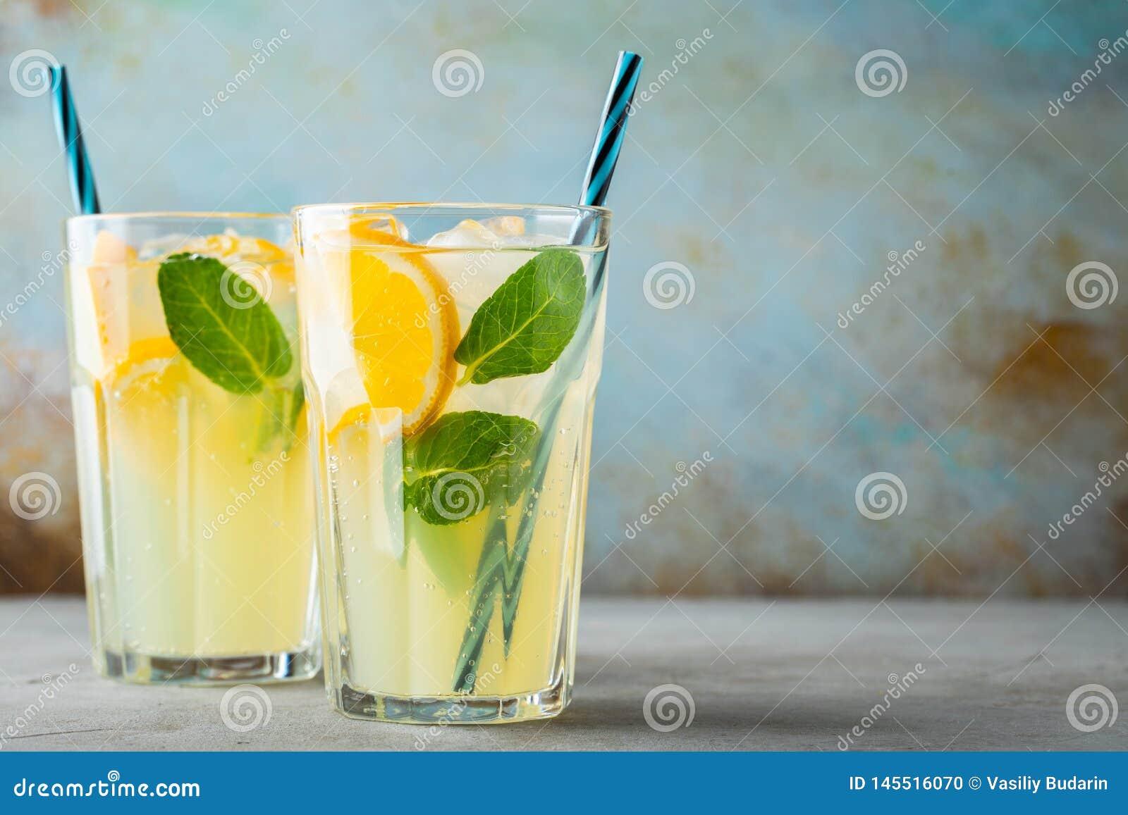 Dos vidrios con limonada o c?ctel del mojito con el lim?n y menta, bebida de restauraci?n fr?a o bebida con hielo en azul r?stico
