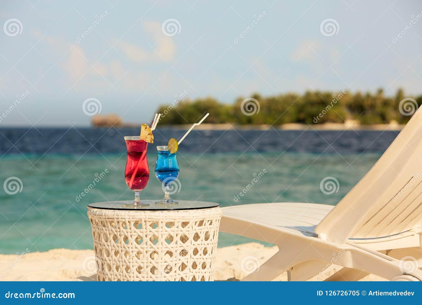 Dos vidrios con los cócteles en la tabla cerca del banco de la playa o de la silla de cubierta con el océano azul y la arena blan